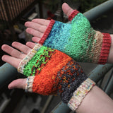 Palm-up view of textured fingerless mitts.  The left shifts from grey to orange to green with speckled orange cuffs, and the right shifts from cream to green to blue with coral cuffs.