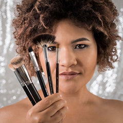 Tash Brooks Owner of Lusid Beauty and award willing makeup artist holding some make up brushes