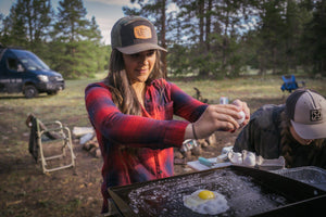 Blackstone Griddle being used to make eggs by a young woman.