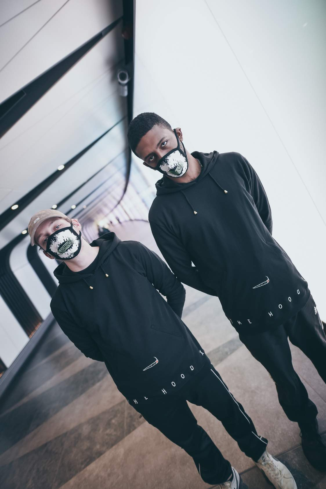 two men wearing black full sleeve hoodie with their face covered with mask paired with a pair of black track pants and white shoes are standing in a subway.