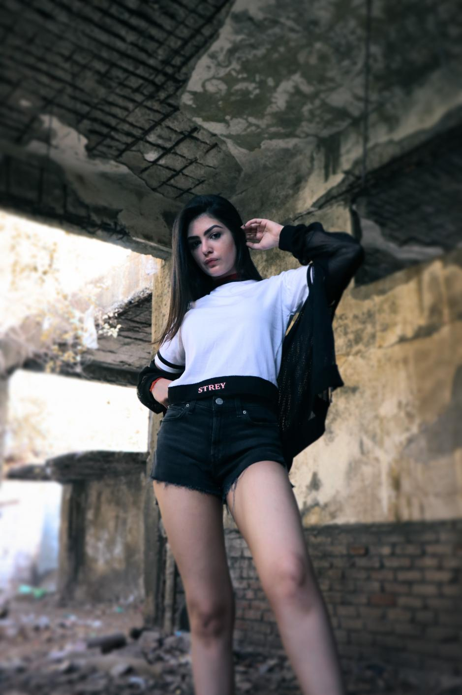A girl wearing black and white round neck short sleeve regular fit T-shirt with black bands on neck sleeves and bottom of the T-shirt and black overcoat paired with shorts is standing in an under construction building.