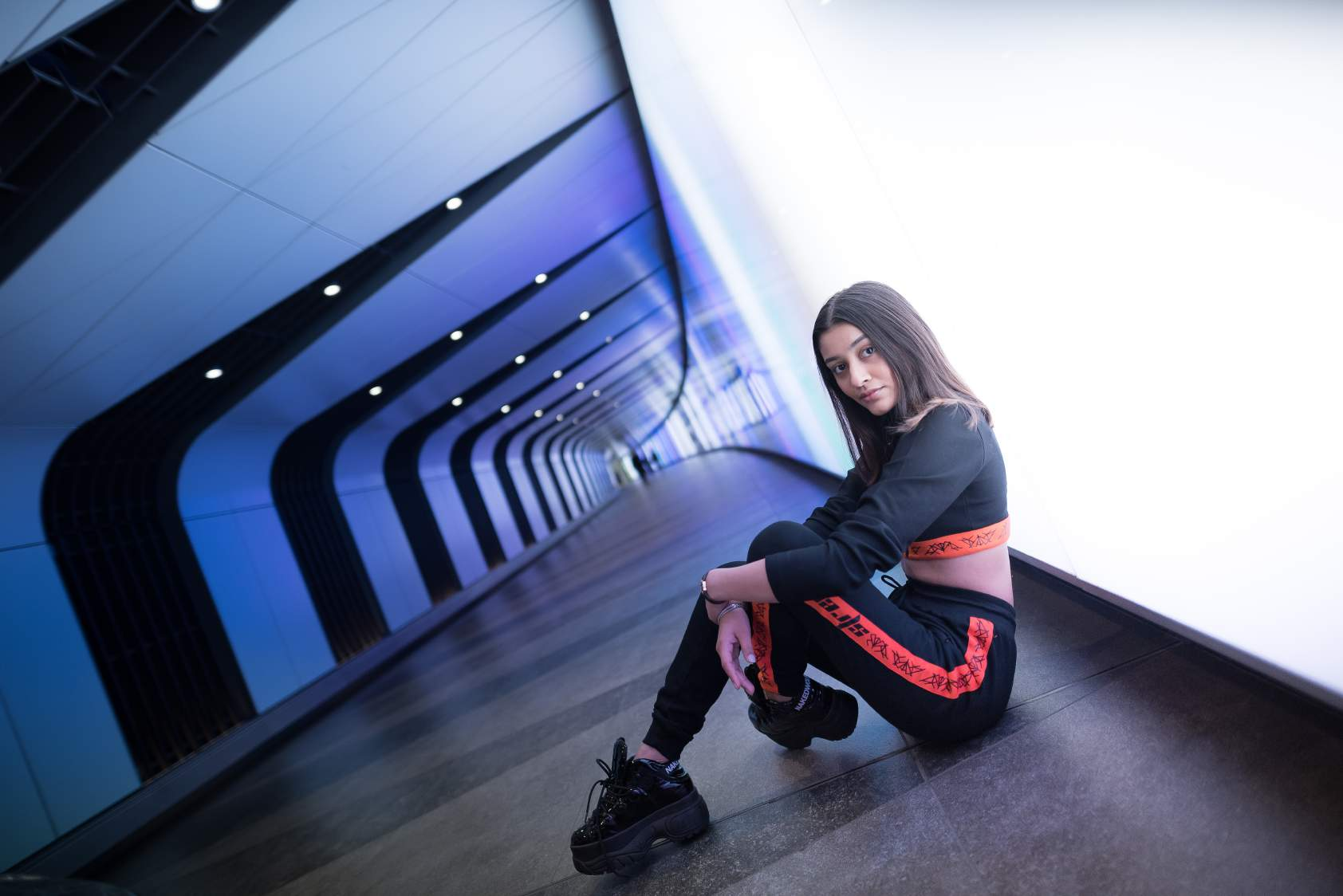 A girl wearing Black colored crop top with orange band at the bottom with a zip in the front and black and orange track pants with orange strips on the side of the track pant and high boots. Sitting in a subway.