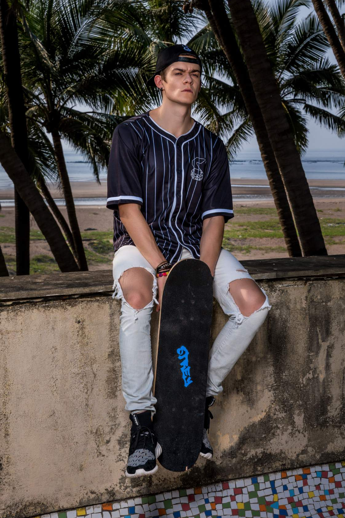 A boy wearing Black stripped short sleeve panther jersey paired with knee torn denim is sitting with a skate board in his hand.