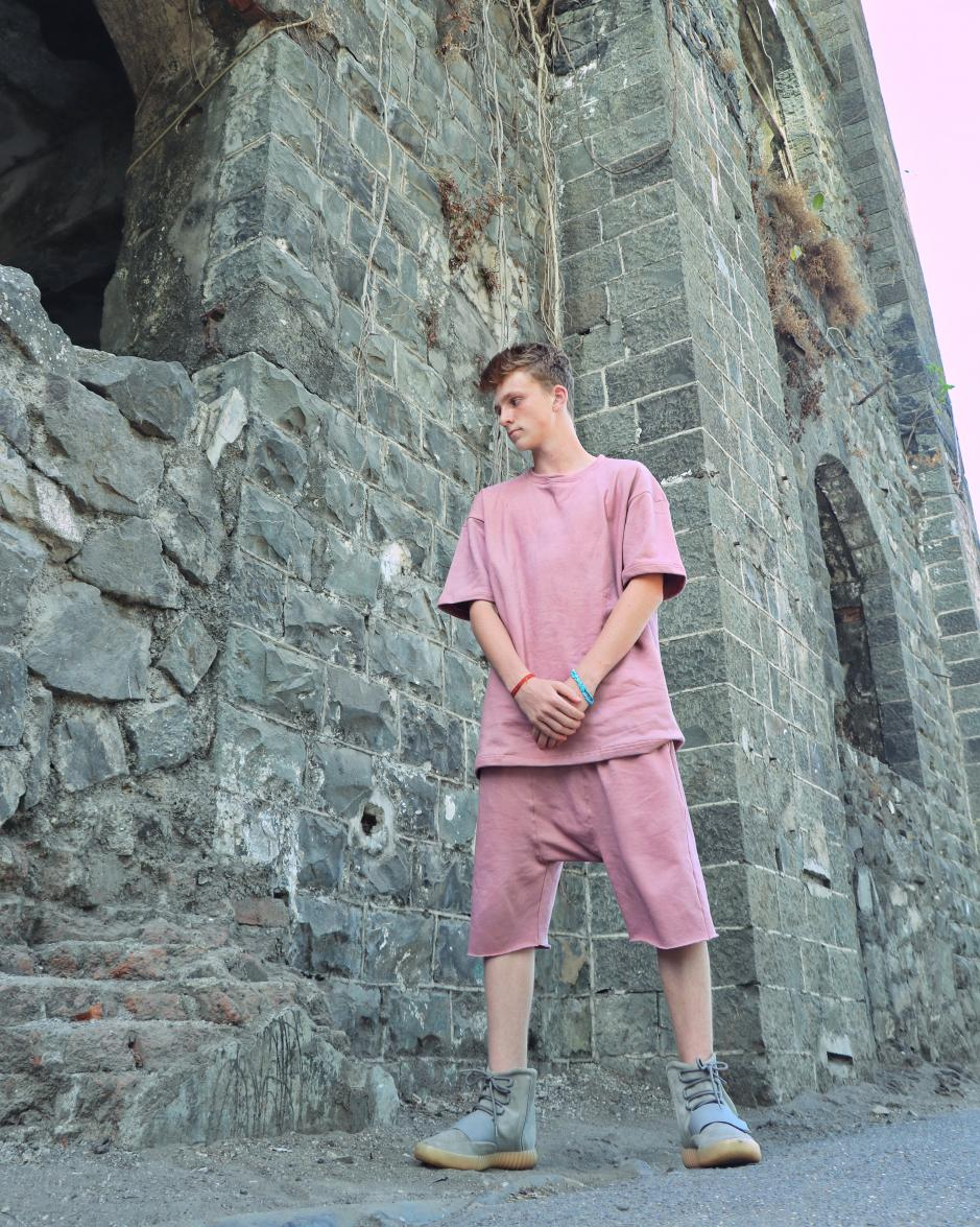 A Boy wearing Faded effect Ashrose Over-sized short sleeve T-shirt and Ash rose Drop Crotch featuring an elastic waist standing in front of a rocked wall.