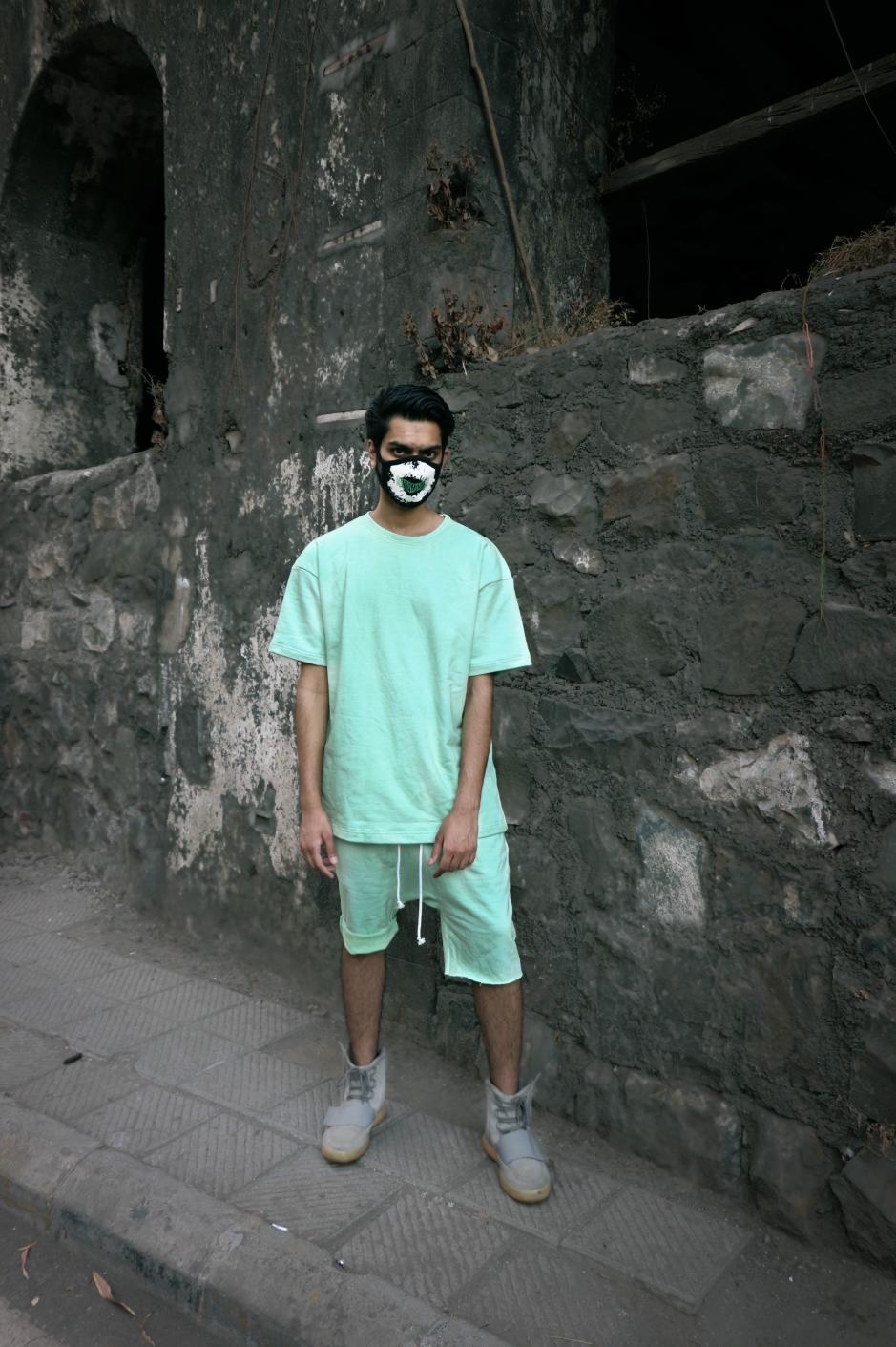 A boy wearing green colored short sleeve round neck T-shirt paired with Green shorts and white shoes is standing in front of a rocked wall.