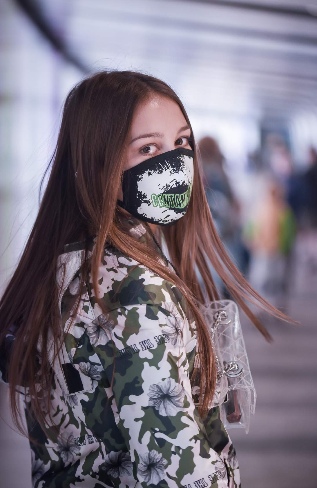 A girl wearing green and white coat and wearing a mask with a transparent sling around her neck is standing in the subway