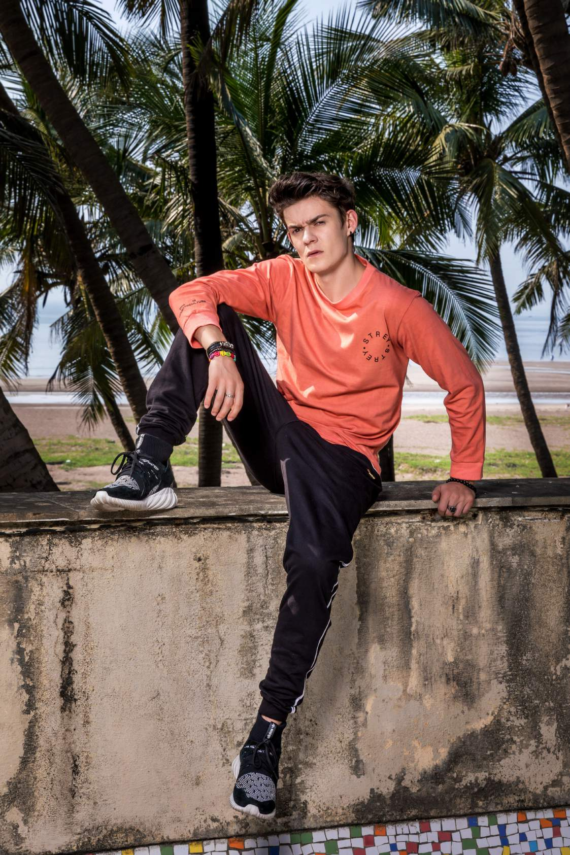A boy Wearing pink full sleeved round neck T-shirt paired with black track pant and shoes is sitting on a wall.