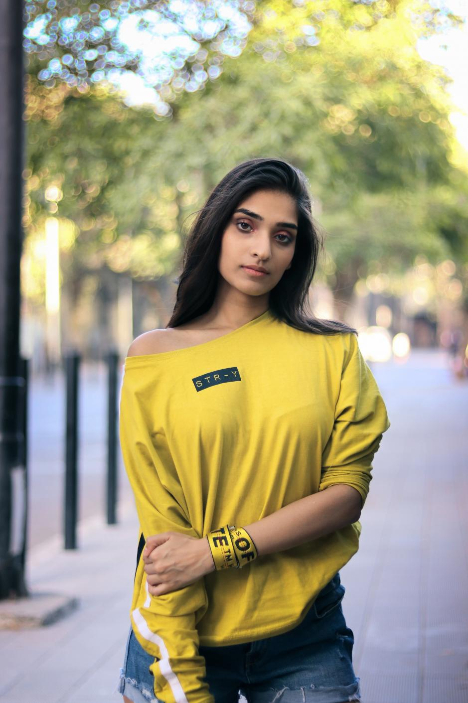 A girl wearing yellow round neck full sleeves T-shirt with white strips on the sleeves and str-y written on it is standing on a footpath