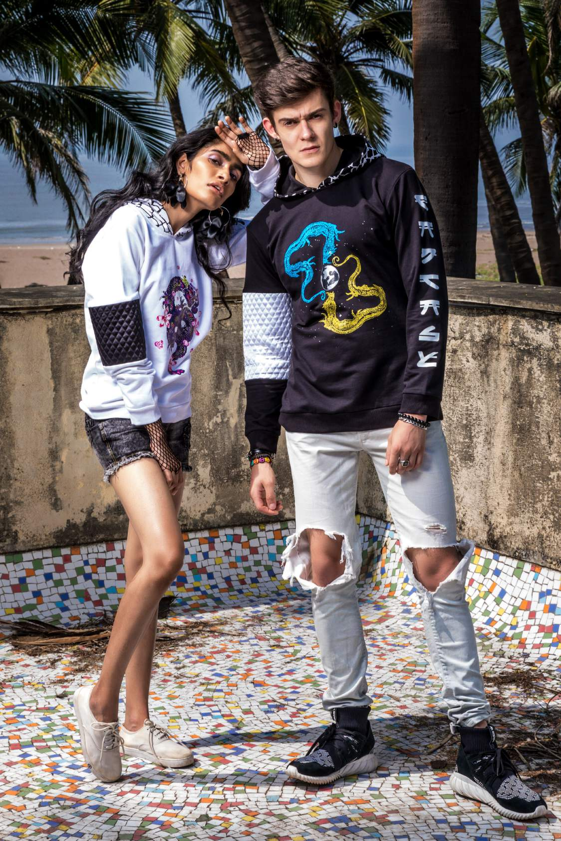A girl wearing white hoodie with a dancing dragon printed on it with a pair of shorts and white shoes is standing with a guy wearing a black hoodie, knee torn denim and black shoes.