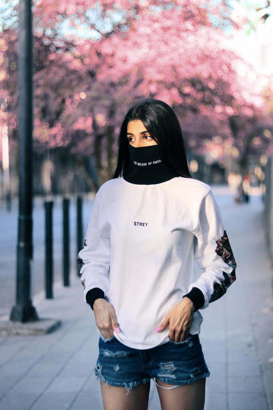 A girl wearing high neck white and black full sleeves regular fit T-shirt with flowers printed on the sleeves paired with shorts.