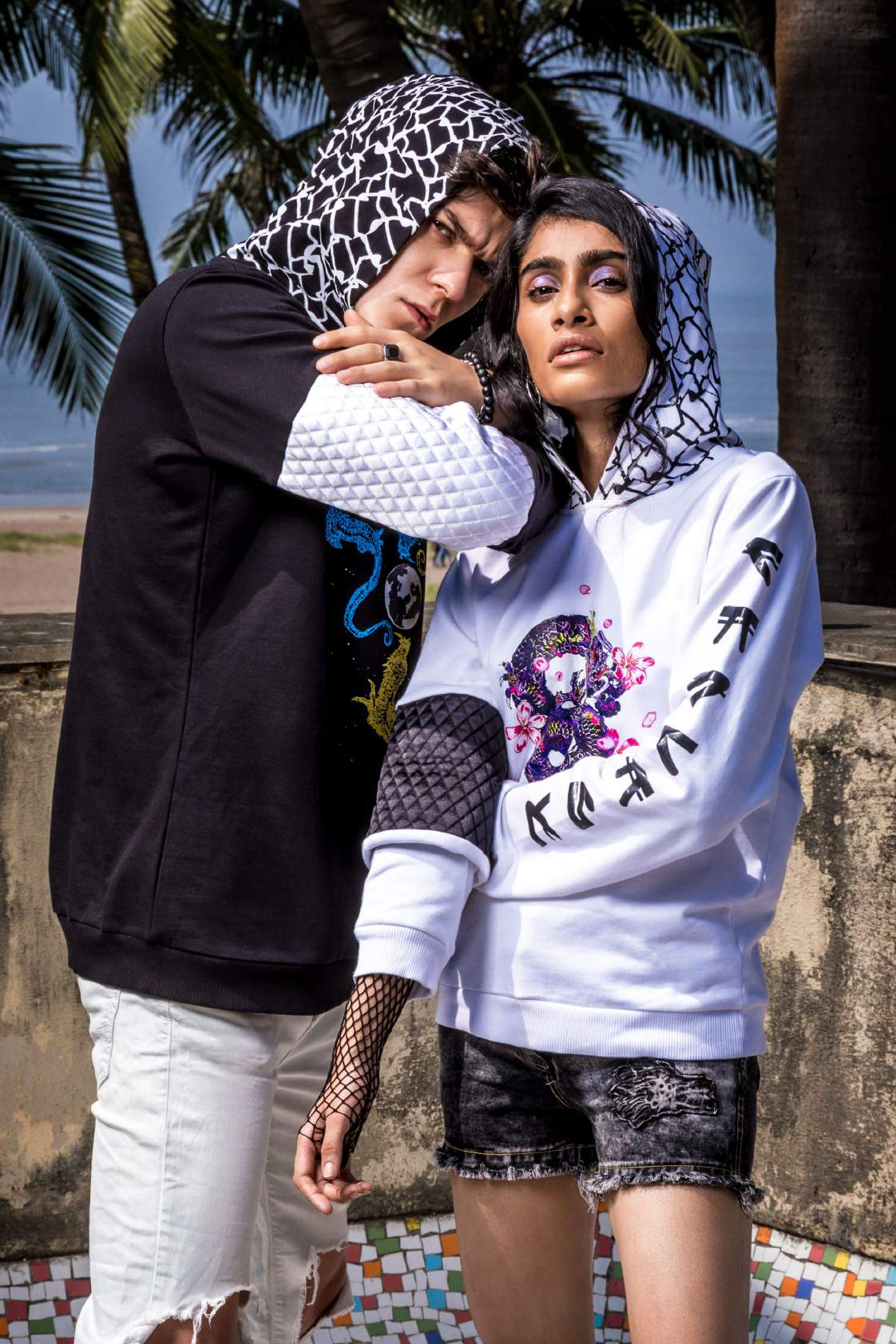 Close up of a boy wearing a black hoodie with moon printed in the center paired with a knee torn denim and a girl wearing white hoodie paired with a shorts.