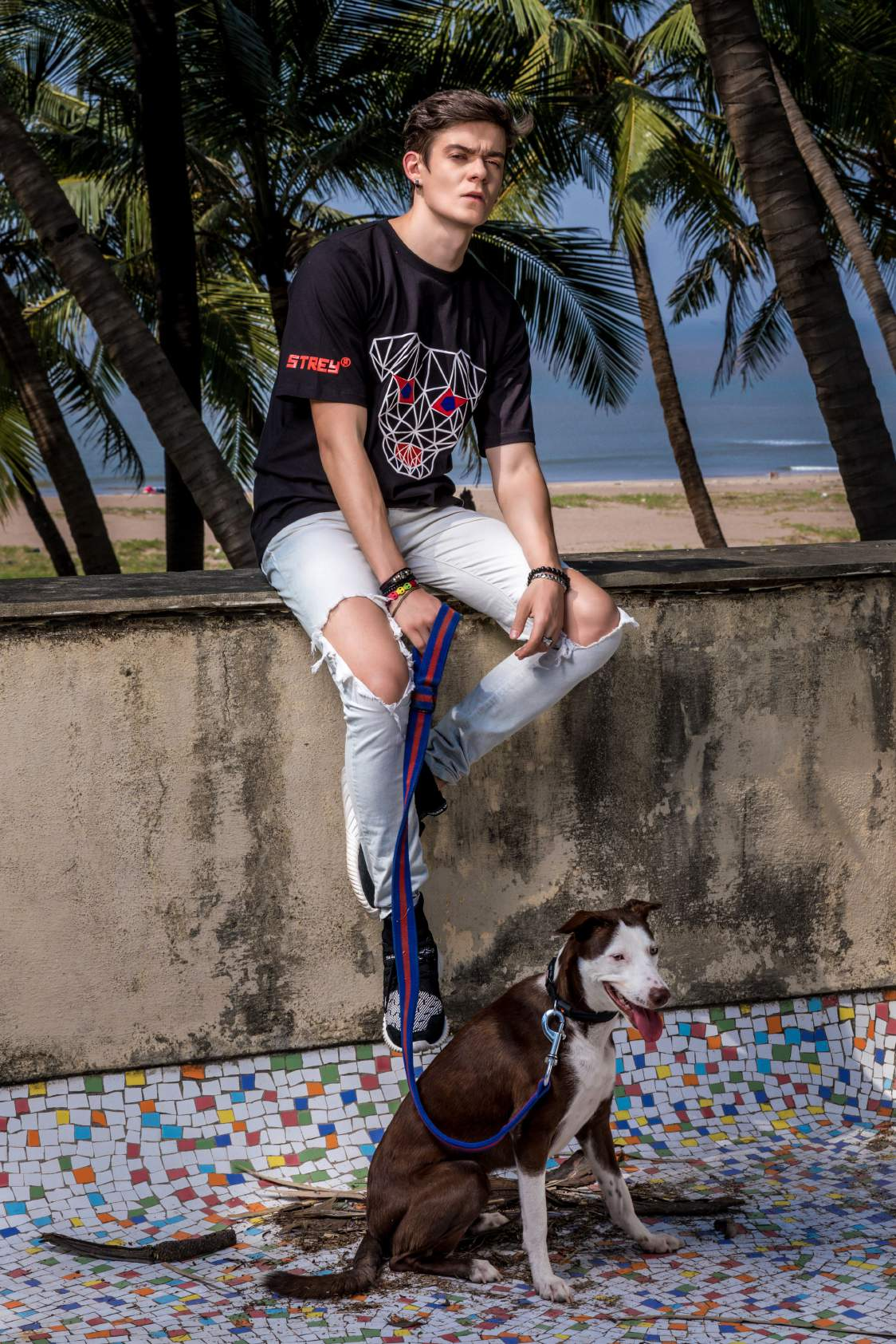 A boy wearing black round neck short sleeves regular fit T-shirt with dog printed on it paired with knee torn denim and shoes is sitting on a wall with a dog near his foot.