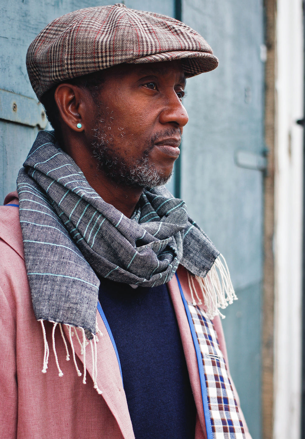 A man wearing a scarf handwoven with naturally dyed organic cotton.