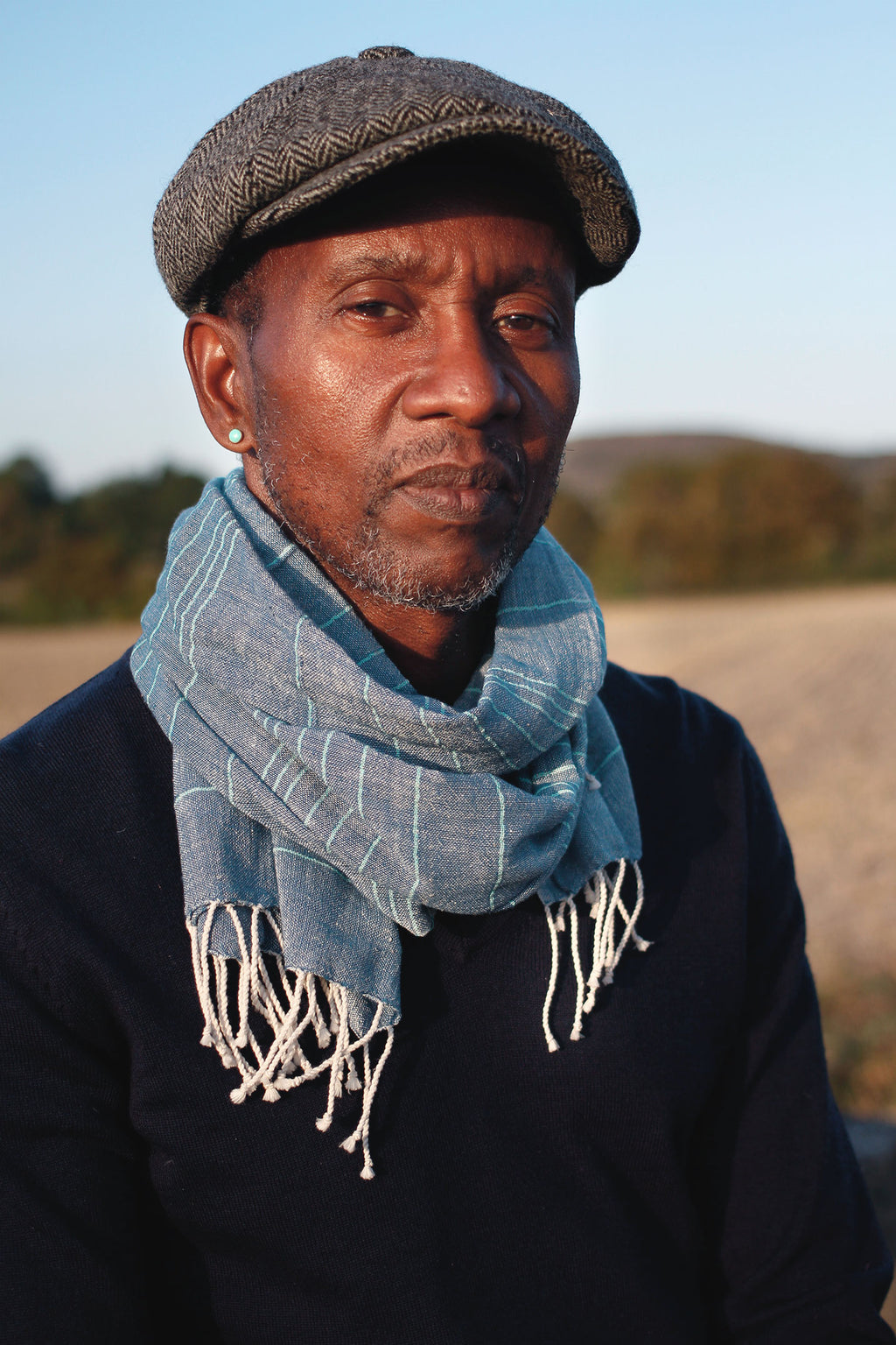 Funky man wearing a blue handwoven cotton scarf with teal lines