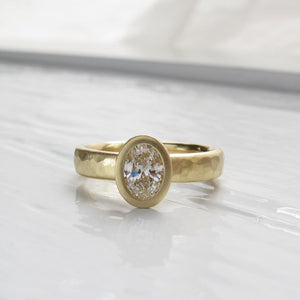 Oval diamond bezel set engagement ring with rustic hammered texture