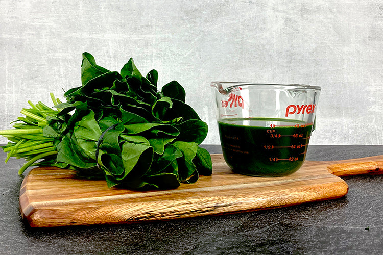 2 bundles of spinach next to one cup of spinach juice