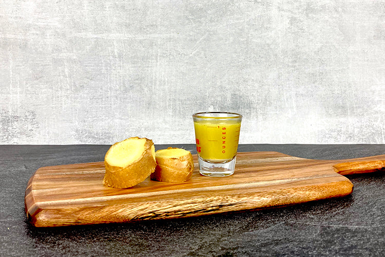 two slices of ginger next to one ounce of ginger juice