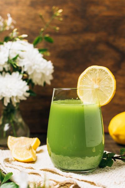green juice with lemon slice and white flowers in background