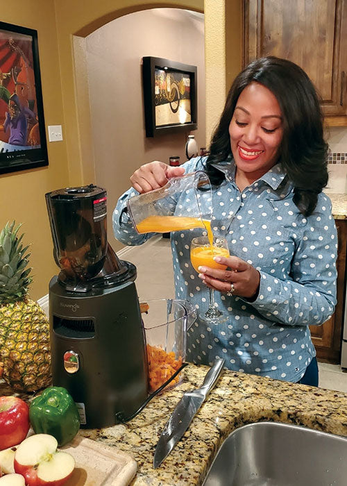 Kuvings Customer Review: Adrianne pours herself a glass of fresh juice.