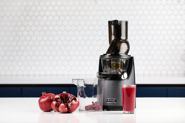 EVO820 juicer and a glass of pomegranate juice on a counter