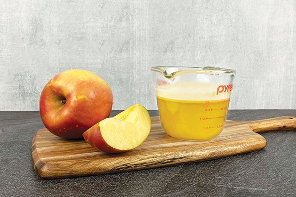 apple and apple slice next to a measuring cup of apple juice