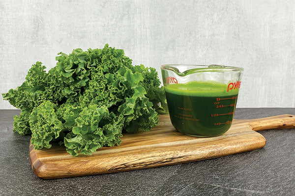 1 bunch of kale next to a measuring cup of kale juice