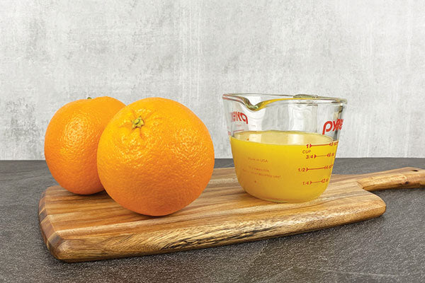 two oranges next to a measuring cup of orange juice