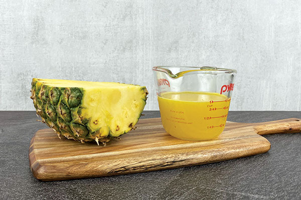 half a pineapple next to a measuring cup of pineapple juice