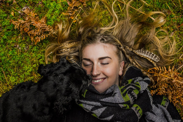 happy dog and girl laying in grass