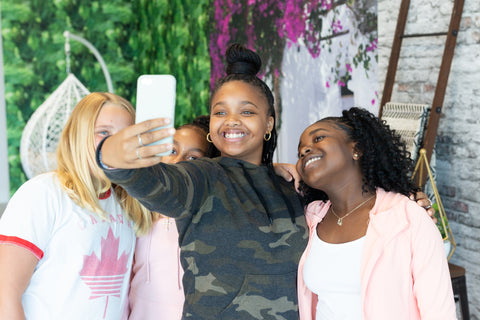 image of girls taking a selfie on their phone