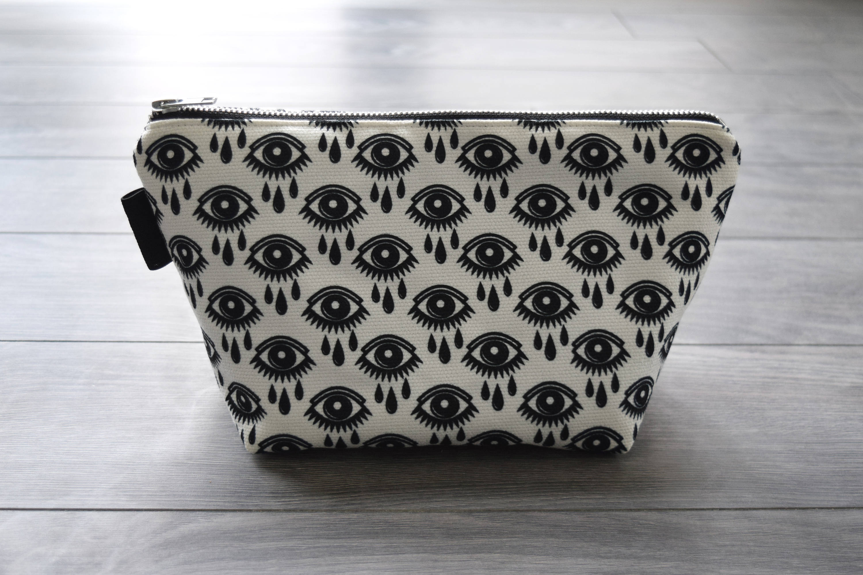 white and black eye print - lined canvas zippered pouch - all over graphic