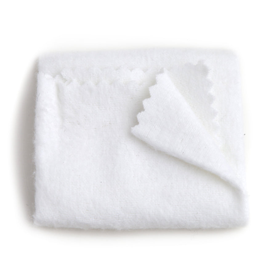 a single white cotton cloth for buffing and polishing against a white background with one corner flipped form top right to the middle of image