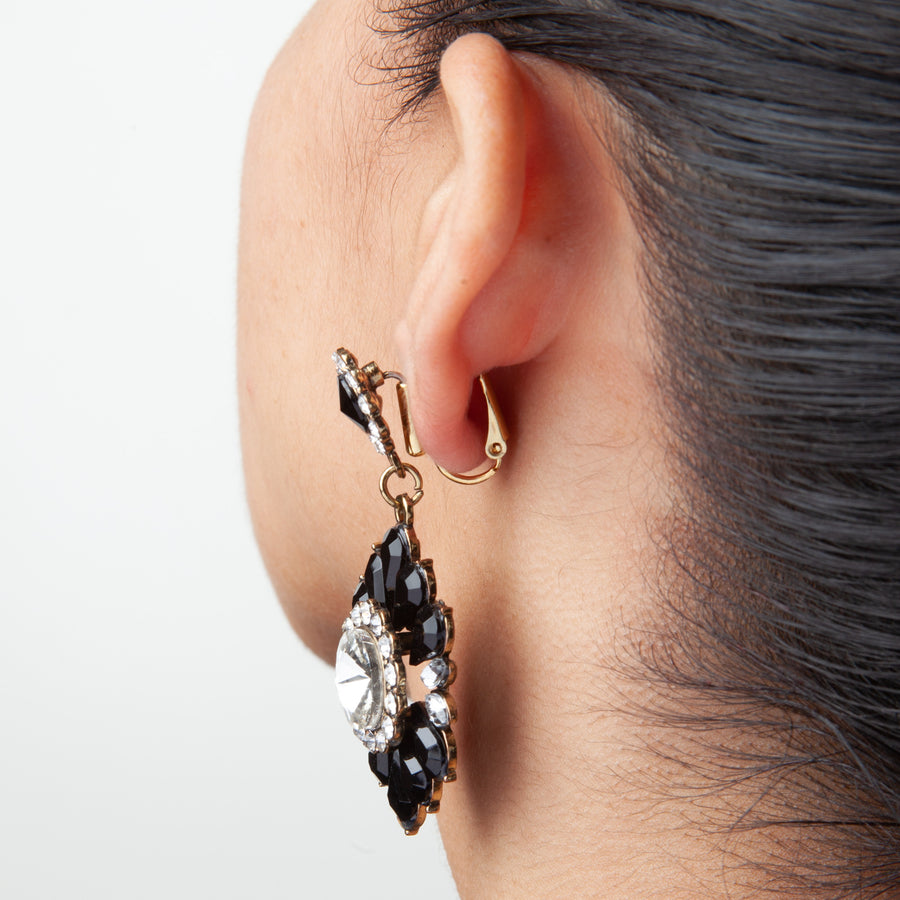 side view of woman's ear with post to clip on earring converters showing a large statement dangle earrings converted to clip on earrings on a white background
