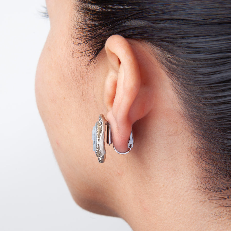 side view of woman's ear with post to clip on earring converters showing a large statement earrings converted to clip on earrings on a white background