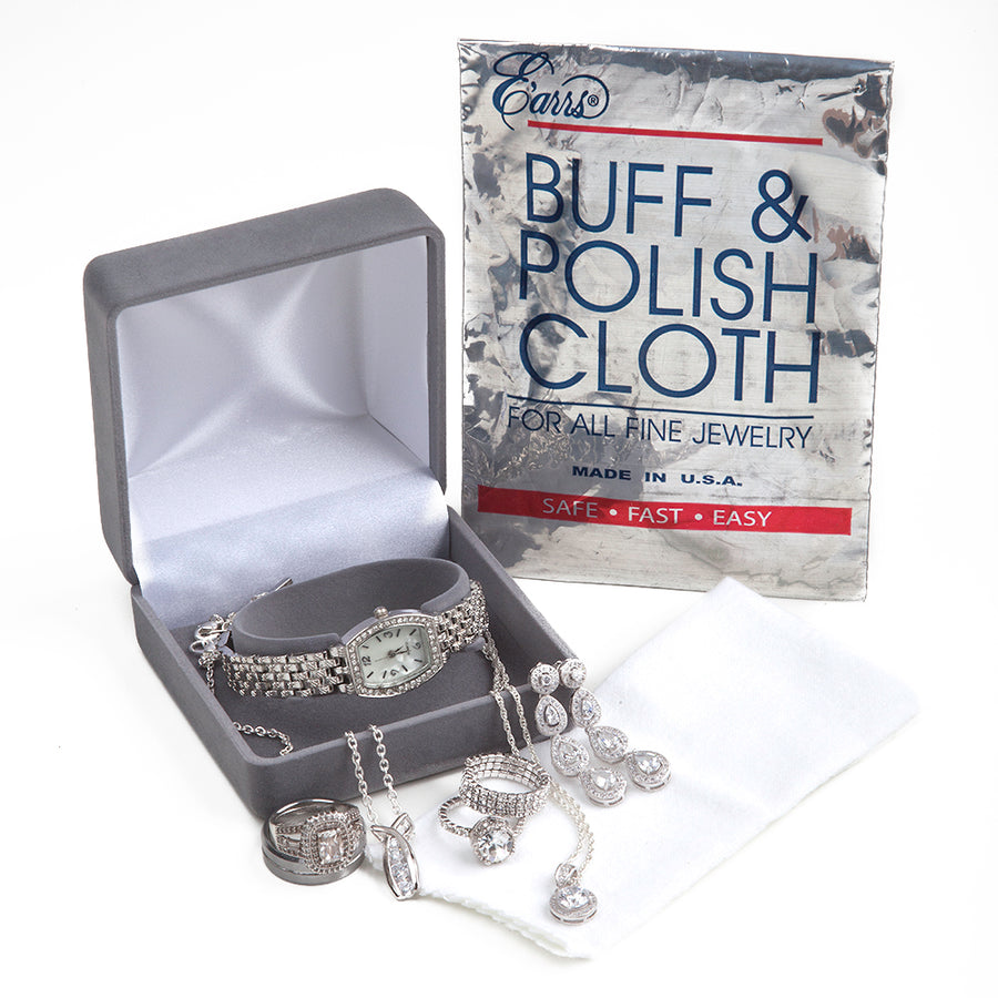 an open box for wrist watches with diamond dangle earrings, a diamond pendant necklace, and diamond rings with a buff and polish cloth from earrs inc next to it and a pouch to store cloth against a white background
