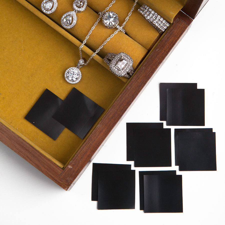 An open jewelry box with green yellow  felt featuring anti tarnish squares from earrs inc and some diamond dangle earrings, a diamond pendant necklace, and two styles of diamond earrings
