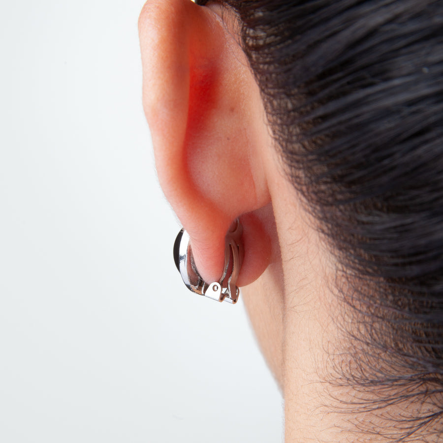 back of left ear of woman with dark hair pulled up with a clip earring on to show what a pair of adhesive clip on earring backings looks like when worn