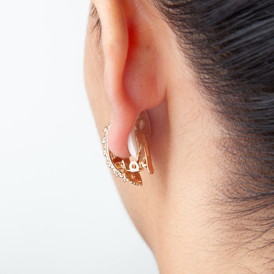bad view of woman's ear showing how clip slips clip on earring cushions look when worn with clip on earrings
