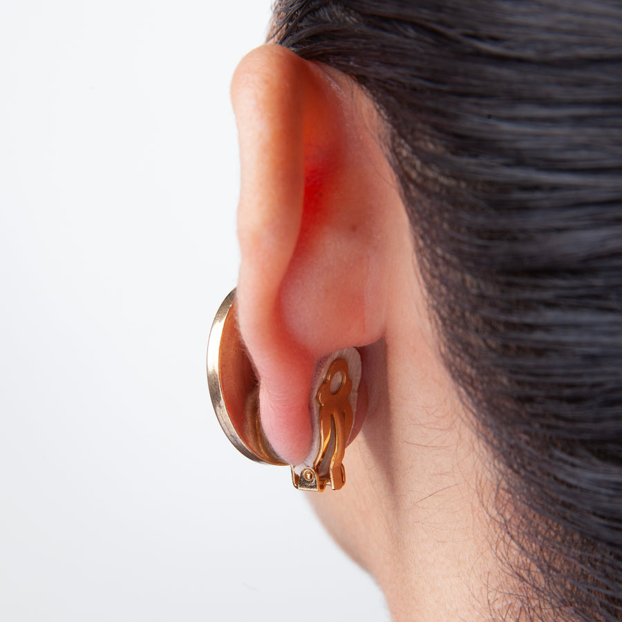 a woman with dark hair pulled up wearing a clip on earring with foam pads in between the earlobe and earring against white background