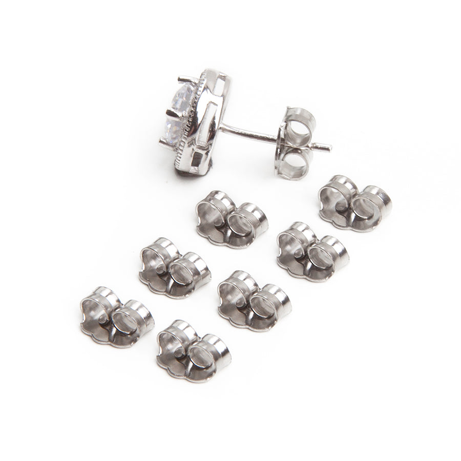 eight butterfly friction earring backs made of stainless steel laid out in two rows of four for a total of eight with an earring in silvertone with large clear diamond in a halo setting against a white background
