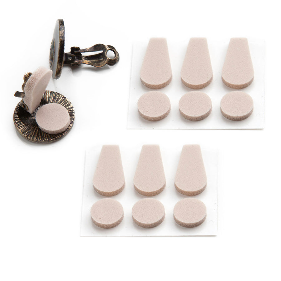 two sheets of foam pads containing three paddle shaped pads and three dot shaped pads next to a pair of clip on earrings where one earring is displaying the foam pads in the correct use against a white background