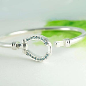 Large horse shoe bangle in Sterling Silver with blue Topaz