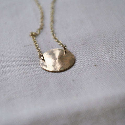 Gold pendant, hammered into a disc shape, on a gold chain