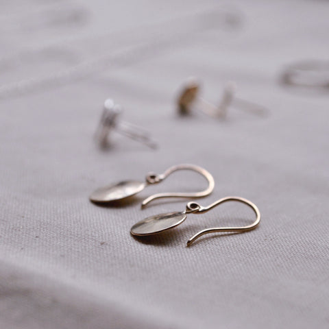Gold Droplet Earrings laying on a natural cotton cloth