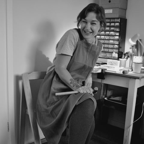 Sarah, sitting at her workbench, holding a hammer and laughing at something just out of frame