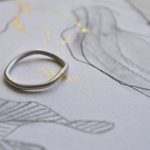 A silver Flow ring with pale gold solder, laying on a pencil and ink sketch