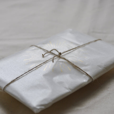 A carefully wrapped package, in natural colours and translucent glassine paper