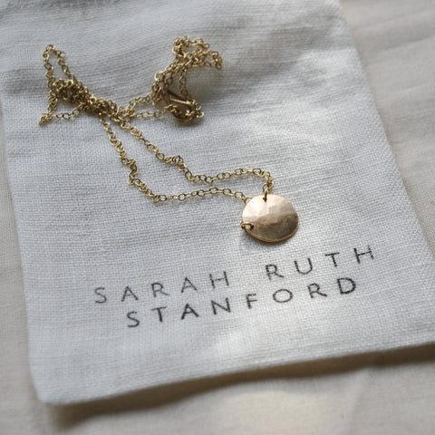 A gold pendant laying on a neat, white, linen bag
