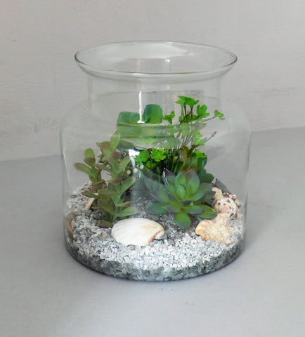 Artificial succulent arrangement in large glass jar