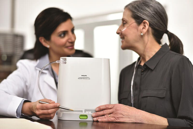 A paitent using simply go mini portable oxygen concentrator  while sitting with doctor